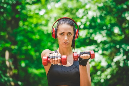 Fitness woman with headphones lifting dumbbells in nature.