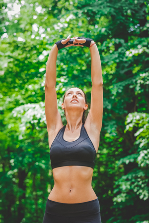 Young female stretching arms in nature. Fitness healthy lifestyle concept.