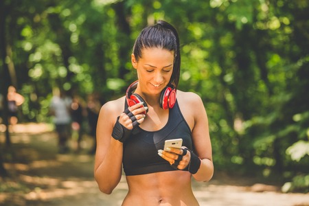 Young woman relaxing after jogging and using smart phone in nature. Runners in the background.