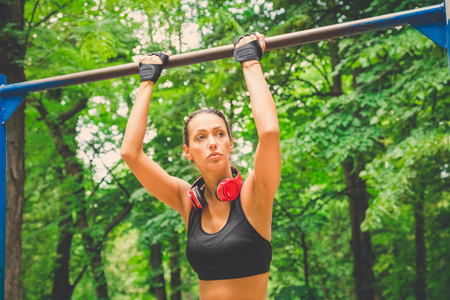 Fitness woman preparing for doing pullups in nature. Healthy lifestyle concept. Reklamní fotografie