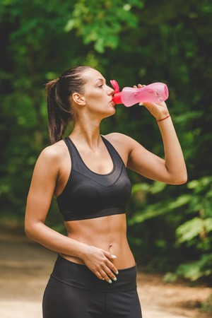 Portrait of athlete woman taking a break and drinking water in nature.