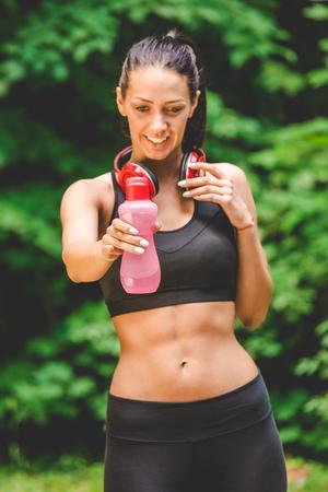 Portrait of female runner holding bottle of water in nature.