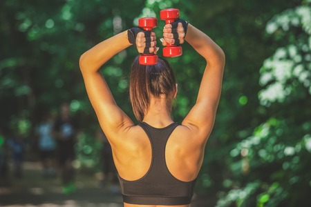 Rear view of sportswoman exercising with dumbbells in nature. Healthy lifestyle concept.