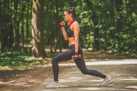 Side view of young female exercising with dumbbells in forest. Healthy lifestyle concept.