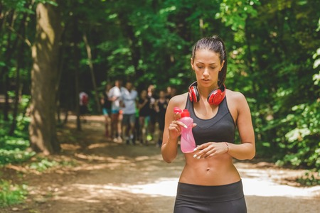 Young athlete walking in woods and holding bottle of water. Group of runners in the background.