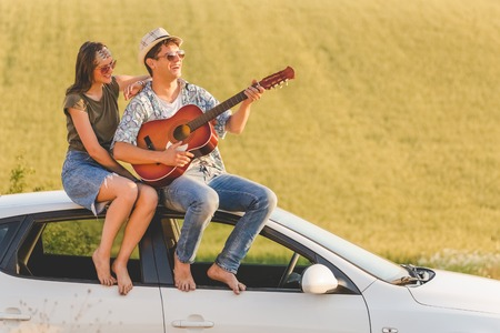 Young hipster couple with acoustic guitar sitting on car roof in nature. Love and travel concepts.