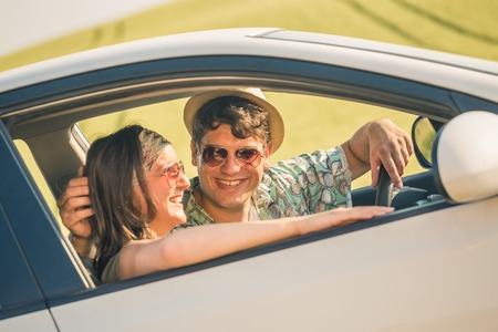 Side view of beautiful couple in car on their summer vacation road trip.