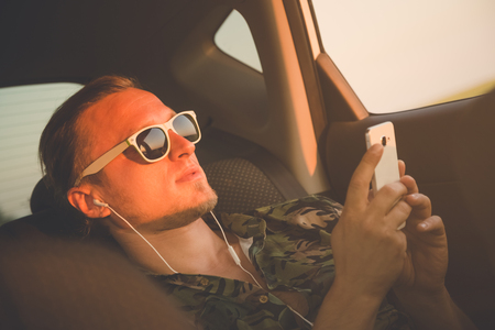 Portrait of young hipster guy sitting on back seat and using smart phone with earphones. Travel and music concepts.