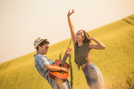 Young couple in love playing guitar and dancing in the field.