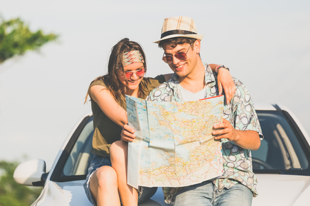Young hipster couple sitting on car hood and looking at map. Travel on the road concept. 版權商用圖片