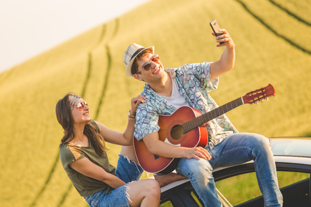 Young hipster couple with acoustic guitar taking selfie while sitting on car roof in nature. 版權商用圖片