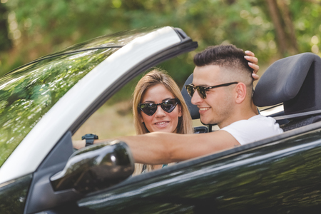 Young couple enjoying road trip inside of their convertible car. 版權商用圖片