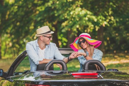 Young couple in love enjoying in their convertible car in nature.