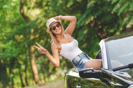 Beautiful young female sitting on cabriolet car in nature and showing winning sign. Travel concept. 版權商用圖片
