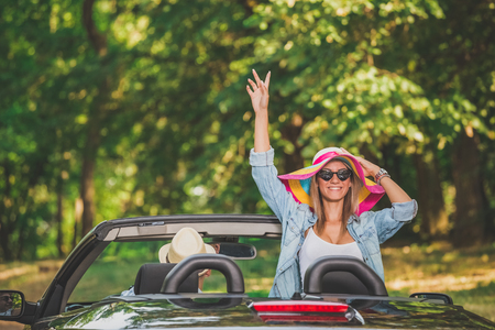 Happy young fashionable woman with raised arm traveling in convertible car with her boyfriend.