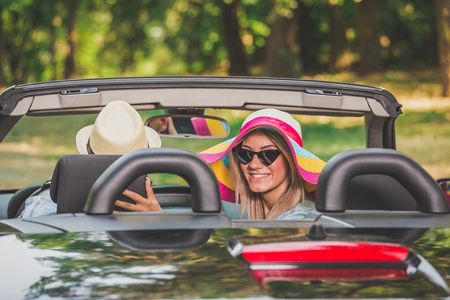 Portrait of young woman enjoying road trip with her boyfriend in convertible car in nature.