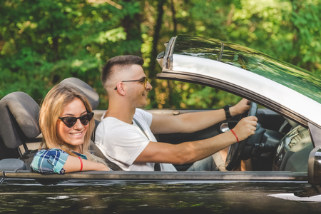 Beautiful couple going on vacation by driving in cabriolet car in nature.