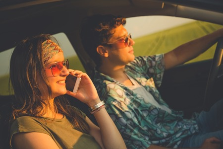 Beautiful couple in car driving and using smartphone. Travel and technology concepts. 版權商用圖片