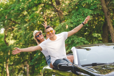 Young fashionable couple in cabriolet car in nature. On the road trip summer vacation concept.
