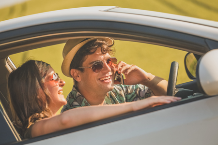 Beautiful couple in car using smartphone. Travel and technology concepts.