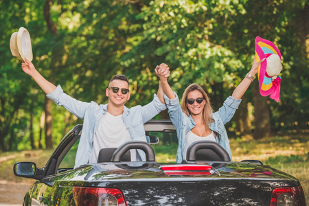 Cheerful couple with hands up in cabriolet car. Road trip travel concept.