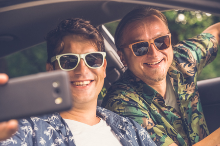 Hipster fashionable guys sitting in car and taking selfie with smart phone.