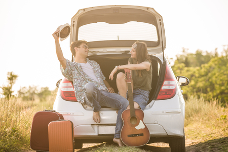 Modern couple taking a break and sitting on car hatchback. Travel and summer vacation concept.