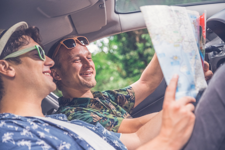 Modern fashionable guys driving a car and looking at road map. Roadtrip travel concept.