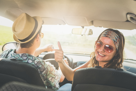 Portrait of young fashionable female with her boyfriend showing thumbs up in car interior.