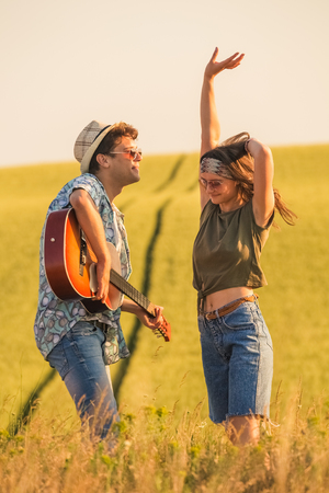 Romantic hipster couple singing their favorite song in nature. Love and summertime concept.