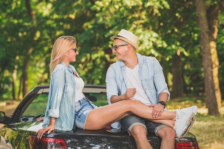 Young couple in love sitting at the back of their convertible car in nature. 版權商用圖片