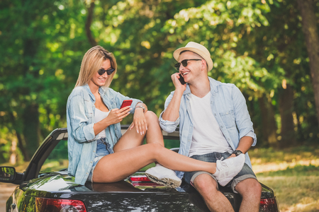 Beautiful fashionable couple sitting at the back of convertible car and using their smart phones.
