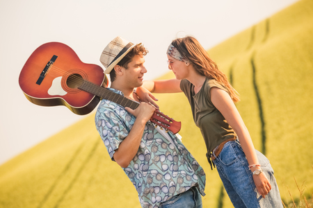 Young fashionable couple with acoustic guitar in nature.