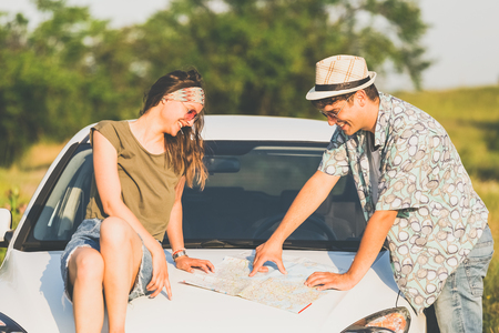 Beautiful couple looking at map on car hood in nature. Summer vacation road trip concept. 版權商用圖片