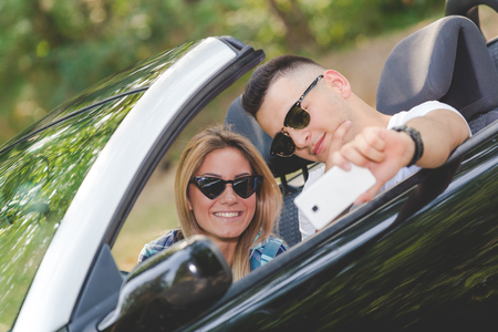 Young couple taking selfie with smartphone while sitting in convertible car. Travel and technology concepts. 版權商用圖片