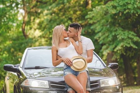 Hermosa joven pareja sentada en el capó del coche y besos. Concepto de romance y viajes.