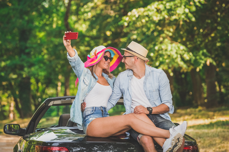 Young couple taking selfie while sitting at the back of their convertible car in nature. 版權商用圖片