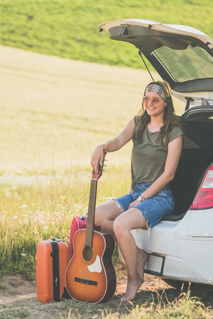 Fashionable woman sitting on car hatchback. Travel and summer vacation concept.