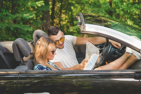 Fashionable young couple sitting in their convertible car and looking at road map. Travel concept. 版權商用圖片