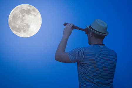 Man looking at full moon with spyglass. Reklamní fotografie