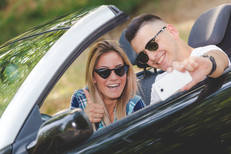 Beautiful couple taking self portrait from their cabriolet car in nature. 版權商用圖片