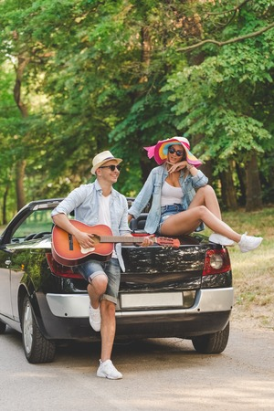 Young fashionable couple playing acoustic guitar on the back side of their convertible car in nature. 版權商用圖片