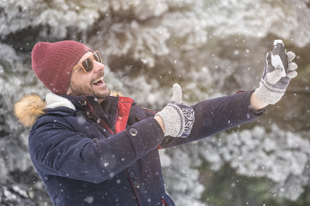 Happy man taking selfie with thumbs up over winter background.