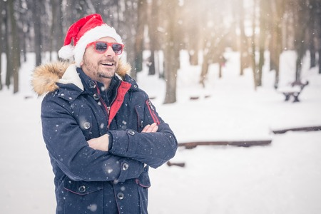 Portrait of man with santa hat and sunglasses in snowy forest. 版權商用圖片