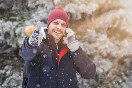 Portrait of young man using smartphone and showing thumbs up on snowy day.