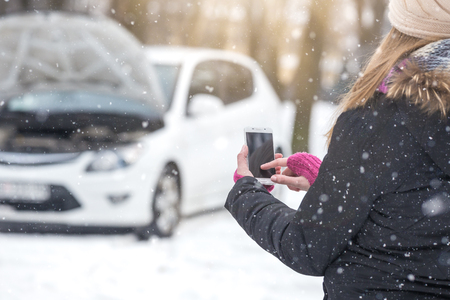 Young woman using blank screen smartphone to call road assistance. Winter and vehicle concept.