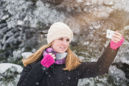 Happy woman taking selfie over winter background.