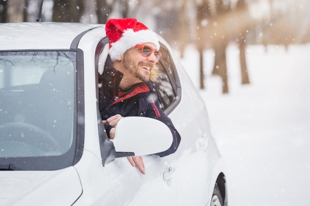 Portrait of car driver with santa hat through car window. On the road winter vacation and holidays concept. 版權商用圖片