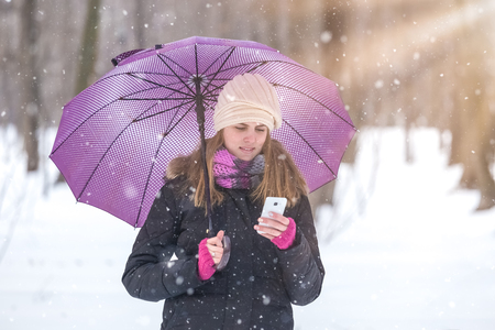 Woman with umbrella using smartphone and enjoying winter season in park.