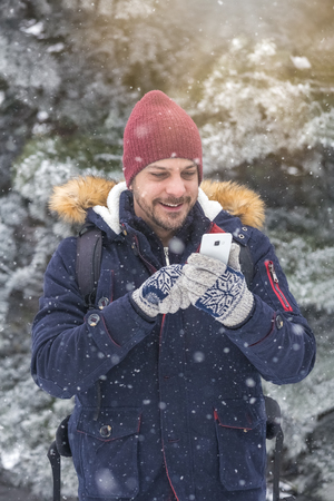 Portrait of young man using smartphone on snowy day. 版權商用圖片